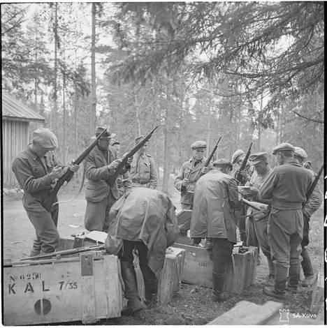 Suomussalmen pitäjän rajakylien asukkaille jaetaan aseita, jotta nämä voisivat puolustautua partisaanien hyökkäyksiä vastaan.