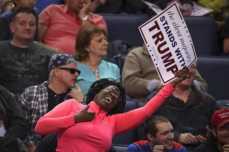 Kannattajat tanssivat Trumpin kampanjatilaisuudessa. Miljardöörin uskotaan voittavan kotiosavaltionsa selvästi.