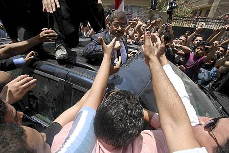 """""""Kaksi pahaa"""" vastakkain Egyptin vaaleissa? """"Äänestän Mursia, koska en halua Shafikin voittavan. Pelkään Mursia, mutta pelkään Shafikia enemmän"""", lausui Kairossa äänestämään saapunut 26-vuotias Nagwan Gamal uutistoimisto AFP:lle. Kuvassa muslimiveljeskunnan presidenttiehdokas Mohammed Mursi kannattajiensa keskellä sen jälkeen, kun hän oli käynyt äänestämässä Zagazigin kaupungissa. Mursin vastaehdokkaana presidentinvaalien toisella kierroksella on syrjäytetyn Hosni Mubarakin aikainen pääministeri Ahmed Shafiq. Monen egyptiläisen mielestä nyt joudutaankin valitsemaan kahdesta pahasta: islamistipresidenttiä ei haluta, mutta toisaalta taas Shafiq on monelle merkki vanhasta vallasta. Moni jättääkin äänestämättä ja monilla Kairon äänestyspaikoilla oli lauantaina hiljaista."""