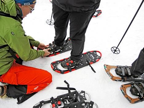 Opas Katariina Okkonen tiukentaa lumikenkien siteitä.