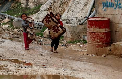 Lapset kantavat tavaroita pakolaisleirillä Sarmadassa, Idlibin maakunnassa, 28. helmikuuta.