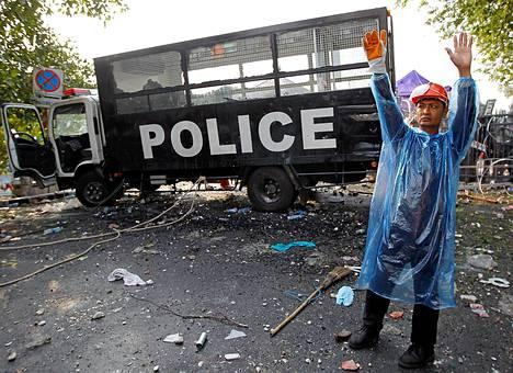 Protestoija viittoo kumppaneitaan lopettamaan kivien heittelyn.