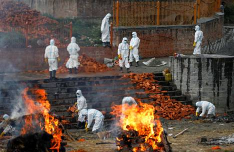 Krematorion työntekijöitä suojapuvuissa Kathmandussa.