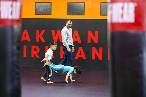 Amirkhani valvoo, kun lapset harjoittelevat kottikärrykävelyä.