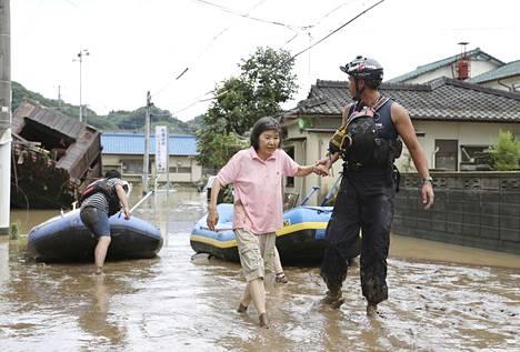 Pelastustyöntekijät auttoivat asukkaita pois tulvivasta korttelista Hityoshin kaupungissa, Kumamaton alueella.