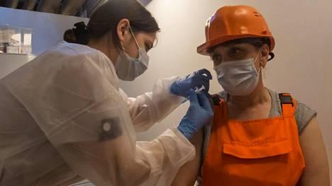 Remonttityöläinen sai koronarokotteen Moskovassa toimivassa rokotuspisteessä.