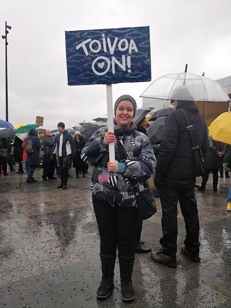 Laura Kantoluoto osallistui mielenosoitukseen toiveikkaan kyltin kanssa.