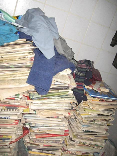 Sanomalehtiä oli kaikkialla asunnossa.