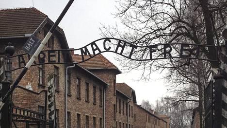 Auschwitzin keskitysleirimuseon portilla on teksti: Arbeit macht frei eli Työ vapauttaa.