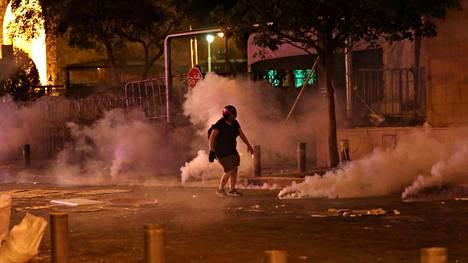 Mielenosoittaja juoksi kyynelkaasun keskellä Beirutissa torstain ja perjantain välisenä yönä.