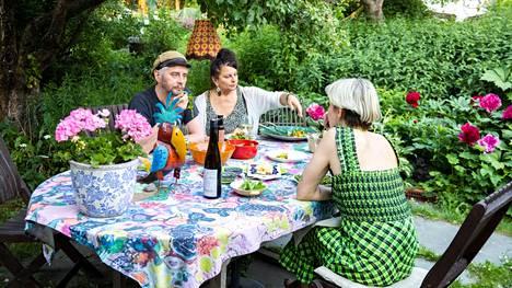 Satu Silvo ja Reidasr Palmgren tarjoilevat puutarhassaan Maria Veitolalle Silvon itse tekemiä mehuja.