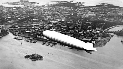 Graf Zeppelin Korkeasaaren yllä Helsingin Pohjoissataman edustalla. Taustalla näkyy eduskuntatalo.