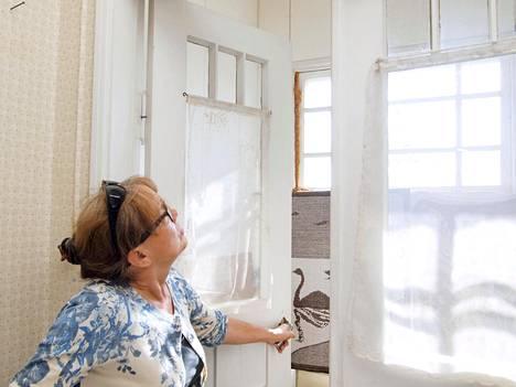 Marja Mikkola talon tuulikaapissa. Taloa kunnostetaan huone kerrallaan.
