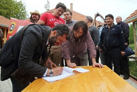 Mies allekirjoittaa Liberlandin kansalaisuushakemusta.