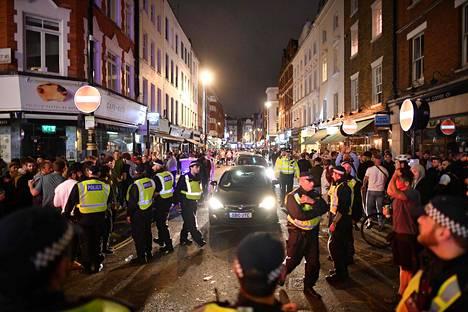 Poliisit raivasivat autoille tilaa kulkea täpötäydessä Lontoon Sohossa.