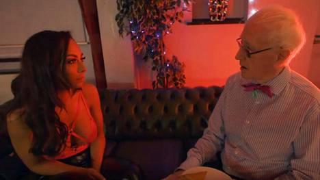 Malika jututtaa parinvaihtoklubin omistajaa Johnia.