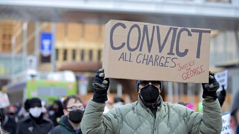 Mielenosoittaja vaati ex-poliisi Derek Chauvinille tuomiota kaikista syytteistä Minneapolisin keskustassa sunnuntaina järjestetyssä protestissa.