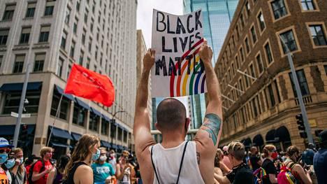 Mielenosoittaja nosti Black Lives Matter -kylttiä Minneapolisissa, Yhdysvalloisa pride-kulkueen aikana sunnuntaina.