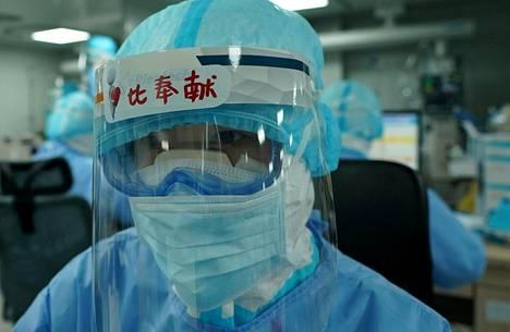 Sairaanhoitaja on pukeutunut suoja-asuun Huoshenshanin sairaalan teho-osastolle Wuhanissa.