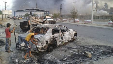Lapset tutkivat palanutta autoa Irakissa Mosulin kaupungissa, jossa on käyty taisteluja Isisiä vastaan.