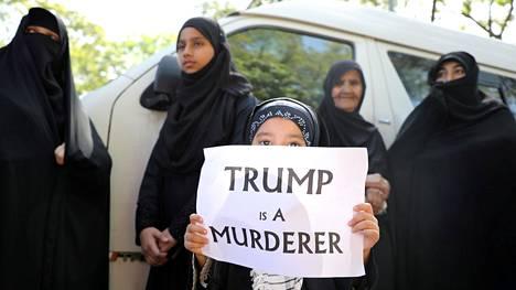 """Pieni tyttö piti kylttiä, jossa luki """"Trump on murhaaja"""" korkea-arvoisen iranilaisupseeri Qassem Soleimanin muistotilaisuudessa. Soleimani sai surmansa ilmaiskussa lähellä Bagdadia tammikuussa."""