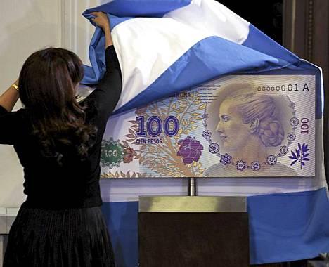 """Evitan kunniaksi. Argentiinan presidentti Cristina Fernández de Kirchner paljastaa uuden 100 peson setelin suurennoksen Casa Rosadan palatsissa Buenos Airesissa. Uudessa setelissä on Argentiinan entisen ensimmäisen naisen Eva Peronin kuva. Tänään torstaina tulee kuluneeksi 60 vuotta Evitana tunnetun Eva Peronin kuolemasta. Eva Peron oli Argentiinan presidentin Juan Peronin vaimo ja kansan keskuudessa erittäin suosittu poliittinen hahmo. Eva Peron kuoli kohtusyöpään 26. heinäkuuta 1952 ollessaan vasta 33 vuoden ikäinen. """"Hän ei ollut täydellinen, hän ei ollut pyhimys. Päinvastoin, hän oli tavallinen nainen, joka löysi paikkansa miehen ja koko kansakunnan rinnalla"""", presidentti Fernandez sanoi uutistoimisto Reutersin mukaan. Eva Peronin elämästä on myös tehty Andrew Lloyd Webberin säveltämä musikaali Evita, josta tehtiin Alan Parkerin ohjaama elokuvaversio vuonna 1996. Elokuvassa Evitaa näytteli Madonna."""
