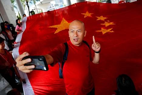 Kiina-mielisten tapahtumaan osallistunut ravintoloitsija Alex Yeung otti selfien Kiina lipun edessä.