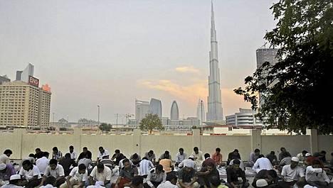 Burj Khalifa näkyy taustalla, kun muslimit aloittavat ruokailun auringon laskiessa.