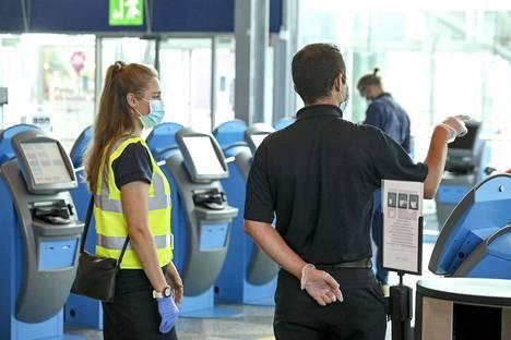 Kasvomaskit ovat lentoasemalla yleinen näky. Lähes kaikki matkustajat ja työntekijät ovat suojautuneet.