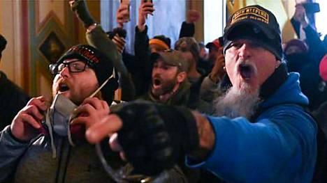 Siniseen takkiin pukeutunut Jon Schaffer tallentui uutiskuvaan väkijoukon vyöryessä sisään Yhdysvaltain kongressirakennukseen 6. tammikuuta.