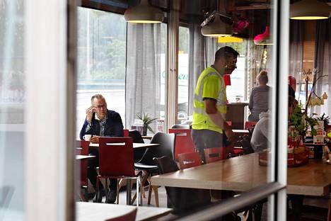 Kirjailija Kari Hotakainen Pakilan Teboilin pöydässä. Makkara on huoltoaseman lounailla suosittu aines.