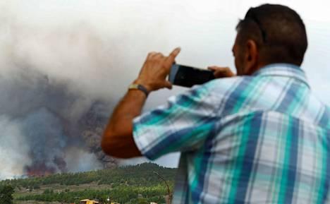 Mies ottamassa kuvaa tulivuorenpurkauksesta nousevasta laavasta ja savusta.