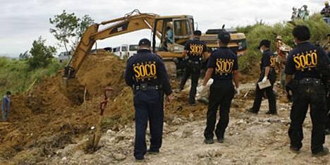 Poliisin tutkijat seurasivat eilen joukkomurhan uhrien ruumiiden etsintöjä.
