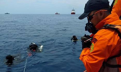 Sukeltajat etsivät mereen pudonnutta konetta.