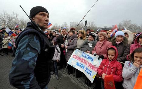 Nämä venäläismieliset mielenosoittajat esittelevät Sevastopolissa kylttiä, jossa lukee Nobel-palkinto Putinille.