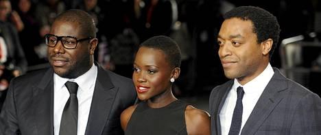 Brittiläinen ohjaaja Steve McQueen (vasemmalla), kenialainen näyttelijätär Lupita Nyongo (keskellä) and brittiläinen näyttelijä Chiwetel Ejiofor (oikealla) saapumassa 12 Years a slave -elokuvan ensi-iltaan.