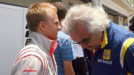 McLarenin Heikki Kovalainen (vas.) ja manageri, Renault'n tallipäällikkö Flavio Briatore keskustelivat varikolla Brasiliassa vuonna 2008.