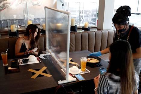 Bangkokissa sijaitsevassa taiwanilaisravintolassa asiakkaiden väliin on pystytetty muoviseinämä. Tarjoilija on varustautunut hengityssuojaimella, visiirillä ja käsineillä.
