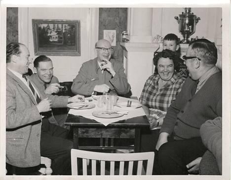 Kansiossa on muutamia kuvia, joiden henkilöt ovat vielä tunnistamatta. Keitä lie tässä iloisessa pöytäseurueessa presidentti Kekkosen lisäksi?