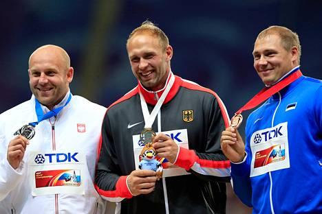 Robert Harting (kesk.) juhli MM-kultaa myös viime kisoissa Moskovassa. Kuvaajasta katsottuna vasemmalla poseeraava hopeamitalisti Piotr Malachowski on nyt Pekingin kisojen ennakkosuosikki.