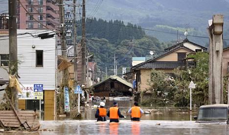 Poliisit etsivät asukkaita tulvan saartamasta rakennuksesta Hityoshin kaupungissa, Kumamaton alueella.