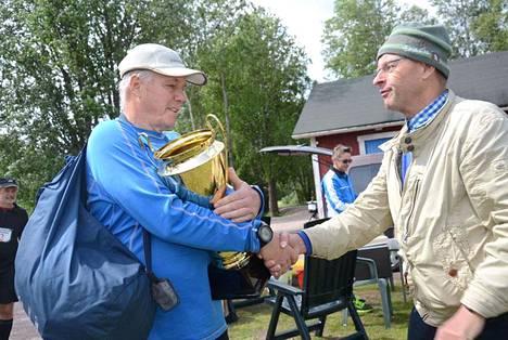 Paloheinän maratonia järjestävä Anders Colliander palkitsi Saukkosen komealla pokaalilla.