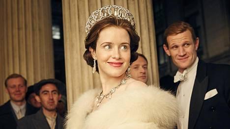 Claire Foy (kesk.) näyttelee Netflixin The Crown -sarjassa Britannian kuningatar Elisabet II:sta. Hänen roolisuorituksensa palkittiin Golden Globe -palkinnolla. Elisabetin aviomiestä, prinssi Philipiä, näyttelee Matt Smith (oik.).