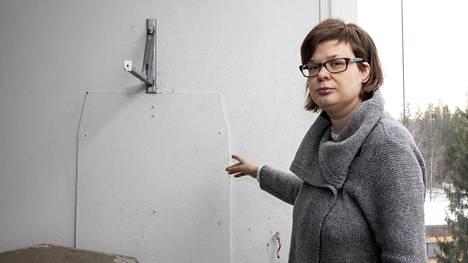 Mari Korhonen ihmettelee parvekkeensa seinässä olevan levyn tarkoitusta.