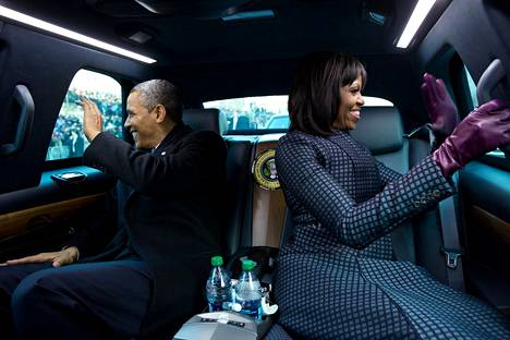 """""""Presidentti ja ensimmäinen nainen vilkuttavat tukijoilleen matkalla virkaanastujaisiin. Olin kysynyt presidentiltä, voinko ajaa heidän kanssaan presidentin limusiinilla. 'Mutta Michellen ja minun oli tarkoitus muhinoida', presidentti vitsaili"""", kuvaaja Pete Souza on kertonut."""