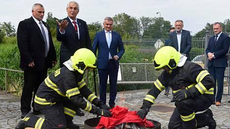 Tshekin pesidentti Milos Zeman (toinen vasemmalta) vahtii, miten palomiehet sytyttävät punaiset, suuret alushousut tuleen. Taiteilijaryhmä veti samat housut kolme vuotta sitten Tshekin presidentinlinnan lippusalkoon protestoidakseen Zemania vastaan.