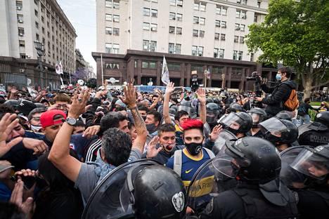 Mellakkavarusteisiin pukeutuneet poliisit muodostivat ketjun ihmispaljouden eteen presidentinlinnan ympäristössä.