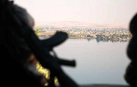 Turkin tukemien syyrialaisjoukkojen taistelija katseli Eufrat-joen yli kurdien hallitsemalle alueelle Pohjois-Syyriassa lauantaina.