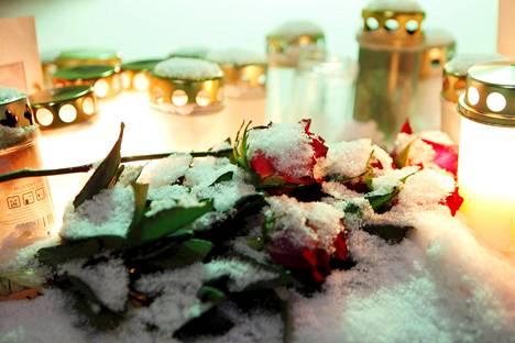 Surmattujen muistoksi jätetyt ruusut olivat jäätyneet pakkasessa Prisman ulko-ovella.