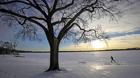 Hiihtäjä ylitti järveä tiistaina Minneapolisissa. Useimmille yhdysvaltalaisille ennätyspakkaset eivät kuitenkaan ole tarkoittaneet mukavaa talviurheilua.